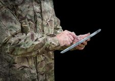 Soldier mid section with tablet against black background with grunge overlay Stock Photo