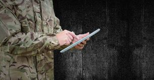 Soldier mid section with tablet against black wood panel royalty free stock photo
