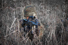 Soldier with military helmet and gun camouflaged in action - snipe shoot Stock Photo