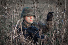 Soldier with military helmet and gun camouflaged in action Stock Photography