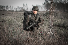 Soldier with military helmet and gun in wilderness. Soldier with military helmet, backpack and trigger in wilderness Stock Images