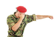 Soldier in military uniform and cap hitting with fist Stock Image