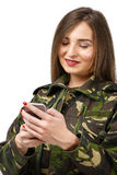 Soldier with a mobile phone in camouflage military uniform. Woman soldier with a mobile phone in camouflage military uniform royalty free stock image