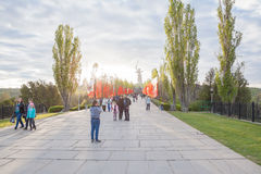 The Soldier monument and The Motherland Calls monument. Volgograd, Russia - May 2, 2015: Tourists walking on Mamayev Kurgan and taking photos against The Royalty Free Stock Image