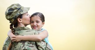 Soldier mother and daughter against yellow background stock photography