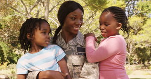 Soldier mother holding her two children in a park