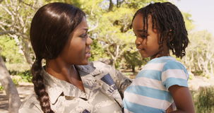 Soldier mother holding his son in a park
