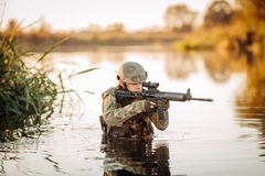 Soldier moving through the water and aiming at the enemy Stock Photos