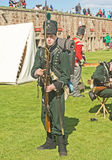 Soldier with musket and bayonet. An image of a soldier from the seventeenth century in authentic uniform holding a musket and bayonet. The re-enactment was stock photos