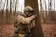 Soldier in forest. Soldier in nato uniform with assault rifle walking in the autumn forest royalty free stock photo