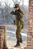 Soldier near wall with a gun. In his hands stock image