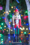 Soldier nutcracker statue standing in front of decorated Christm Stock Images