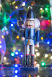 Soldier nutcracker statue standing in front of decorated Christm Stock Photos