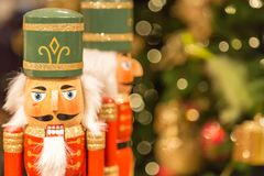 Soldier nutcracker statues standing in front of decorated Christmas tree with bokeh lights Royalty Free Stock Photography