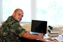 Soldier in office. A soldier working in office using laptop and books Stock Photos
