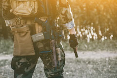 The soldier in the performance of tasks in camouflage and protective gloves holding a gun. Royalty Free Stock Images
