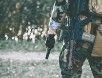 The soldier in the performance of tasks in camouflage and protective gloves holding a gun. Stock Images