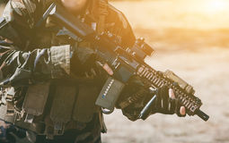 The soldier in the performance of tasks in camouflage and protective gloves, holding a gun. royalty free stock photo