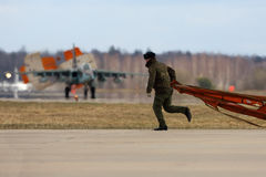 Soldier picks up dropped parachute of Sukhoi Su-25 airplane of Russian air force during Victory Day parade rehearsal Royalty Free Stock Photos