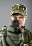 Soldier with pistol aiming. Young soldier with camouflage uniform aiming the target, studio shoot royalty free stock image