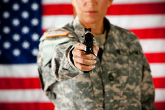 Soldier: Pointing Gun at Camera. Series with a female as a solidier in an United States Army uniform.  Numerous props convey a variety of concepts Royalty Free Stock Photography