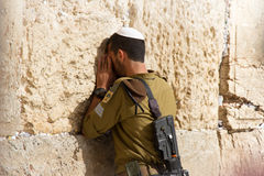 Soldier praying at the Wailing Wall with weapon, Jerusalem, Israel Stock Photo