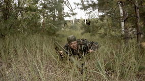 Soldier prepares RPG lying in the grass, and then aiming stock video footage