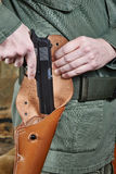Soldier puts gun in holster Royalty Free Stock Photography