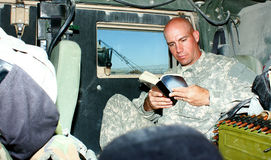 A soldier reading a book. Insight a military armored bulletproof vehicle, surrounding with equipments Stock Photography