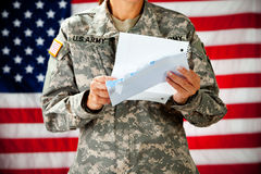 Soldier: Reading a Letter From Home. Series with a female as a solidier in an United States Army uniform.  Numerous props convey a variety of concepts Royalty Free Stock Image