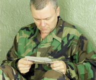 Soldier reading letter from home. Unshaven deployed soldier taking a moment to read a letter from home.  It is not uncommon for deployed soldiers to go days at a Stock Images