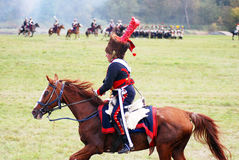 A soldier-reenactor rides a brown horse. Stock Photo