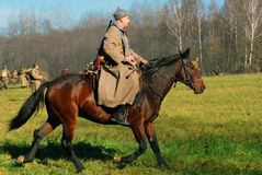 A soldier-reenactor rides a brown horse Stock Images