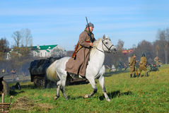 A soldier-reenactor rides a white horse Royalty Free Stock Image