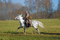 A soldier-reenactor rides a white horse Stock Photography