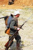 A soldier-reenactor runs holding a gun. Stock Images
