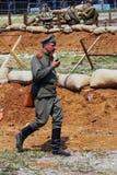 A soldier-reenactor walks and speaks via radio set Royalty Free Stock Photography