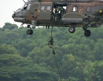 Soldier Repelling From Helicopter. Airshows are popular in Asia, Singapore hosts such events yearly. This image shows a soldier repelling from a Super Puma Royalty Free Stock Images