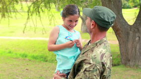 Soldier reunite with his daughter. In park stock footage