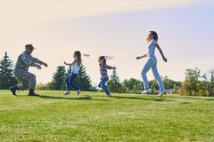 Soldier is reuniting with his family outdoor. royalty free stock image