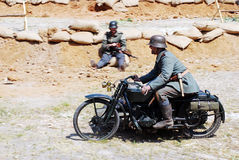 A soldier rides a motorbike. Stock Images