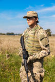 Soldier with a rifle. In the field Royalty Free Stock Image