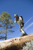 Soldier With Rifle Standing On Tree Trunk. Low angle view of a soldier with rifle standing on tree trunk Stock Image