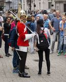 Soldier of Royal Horse Guards in London, surrounded by tourists taking photos. A soldier of Royal Horse Guards Regiment with his sword drawn, wearing stock images