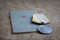 Soldier`s book and a medal for military merit on a tarpaulin. Close-up, the memory of the war. May 9 stock photo