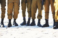 The soldier`s footwear of the Israeli army which is put on legs in clear sunny day. The soldier`s footwear of the Israeli army which is put on legs in clear royalty free stock images