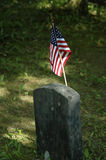 Soldier's Grave. An small, old tombstone with an American flag attached stock photography