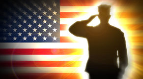 Soldier salutes the American flag in the background. royalty free stock image