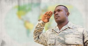 Soldier saluting against blurry map with grunge overlay Royalty Free Stock Images