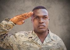 Soldier saluting against brown background with grunge overlay Royalty Free Stock Photos